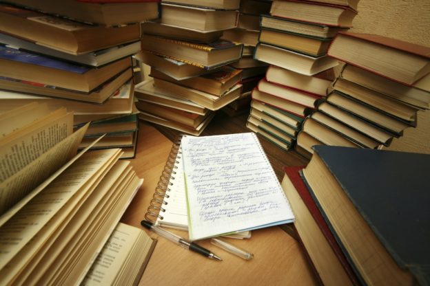 stack of books surrounding notepad