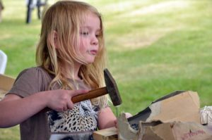 child with messy hair using a hammer on a craft