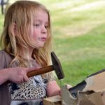 image of young child with messy hair hammering a craft